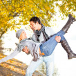 Stock Photo: Happy couple in fall under leaves