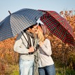 Couple kissing under umbrellas in the park. — Stock Photo