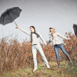 Woman and man with umbrellas during strong wind - Lizenzfreies Foto