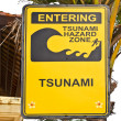 Big yellow tsunami sign on a wooden post on beach in Bali - Stock Photo