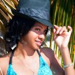 Beautiful caribbean woman with black hat  posing under the palm - Lizenzfreies Foto