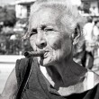 Old wrinkled woman with red flower smoking cigar.  Cuba - Stock Photo
