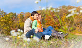 Sweet couple sitting on a hill at the autumn landscape — Stock Photo