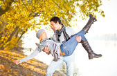 Happy couple in fall under leaves — Stock Photo