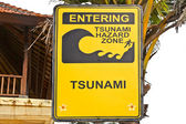Big yellow tsunami sign on a wooden post on beach in Bali — Photo