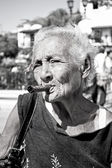 Gamla skrynkliga kvinnan med röd blomma röka cigarr. kuba — Stockfoto