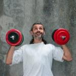Happy man lifting dumbbell — Stock Photo