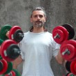 Man lifting dumbbells  with motion blur - Stock Photo