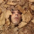Man's face among the autumn leaves — Stock Video
