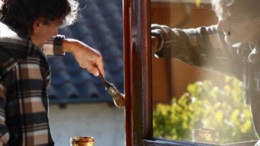 Maintenance worker painting wooden window — Stock Video