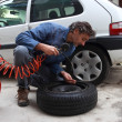 Inspecting the tire pressure — Stockfoto