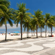 Stock Photo: View of Copacabanbeach with palms and mosaic of sidewalk in Rio de Janeiro
