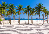 View of Copacabana beach with palms and mosaic of sidewalk in Rio de Janeiro — Stock Photo