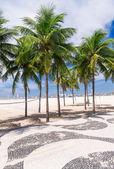 View of Copacabana beach with palms and mosaic of sidewalk in Rio de Janeiro — Stock Photo