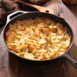 Scalloped potatoes in rustic iron skillet — Stock Photo