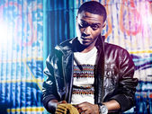 Black youth with jacket and colorful lights — Stock Photo