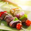 Grilled beef shishkabobs on green plate — Stock Photo