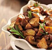 Rosemary herb potatoes in white baking dish close up. — Stock Photo