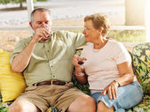 Elderly couple drinking on patio — Stockfoto