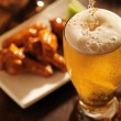 Pouring beer with chicken wings — Stock Photo #33580983
