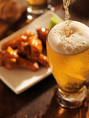 Pouring beer with chicken wings — Stock Photo