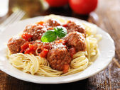 Spaghetti and meatballs with basil garnish — Stock Photo