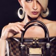 Beautiful blonde woman holding a bag — Stockfoto
