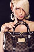 Beautiful blonde woman holding a bag — Stock Photo