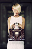 Beautiful blonde woman holding a handbag — Stock Photo