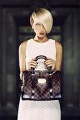 Beautiful blonde woman holding a handbag — Stock Photo