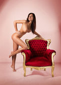 Young sexy brunette posing with old nice chair — Stock Photo