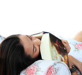 Tired young woman taking a nap at home lying on sofa with a book — Foto de Stock