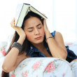 Tired young woman taking a nap at home lying on sofa with a book — Stock Photo #47302375