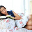 Tired young woman taking a nap at home lying on sofa with a book — Stock Photo #47302379