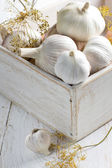 Garlic in a shabby wooden box on the kitchen table — Stock Photo