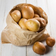Potatoes in paper bag on vintage wooden table — Stock Photo