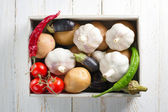Some vegetables in wooden box on vintage wooden table. Garlic, Potato, Chili Pepper, Tomato, Eggplant — Stock Photo