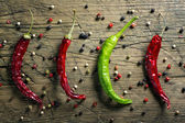Red and green chili peppers and pepper mix on vintage wooden table background — Stock Photo