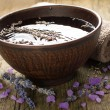 Bowl of pure water and lavender petals on the old wooden surface. Spa treatments composition — Stock Photo #12730879