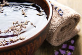 Bowl of pure water and lavender petals on the old wooden surface — Stock Photo