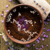 Bowl of pure water and lavender petals on the old wooden surface. Spa treatments composition — Stock Photo