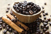 Coffee beans and cinnamon on vintage wooden table — Stock Photo