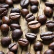 Coffee beans on the vintage wooden table — Stock Photo