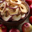 Dried apples in bowl on rustic kitchen table — Stock Photo