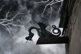 Frightening chimera on the facade of the old castle under thunderclouds and lightning — Stock Photo