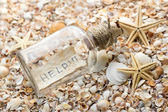 "Romantic postcard with message ""help"" in glass bottle on the beach — Stock Photo"