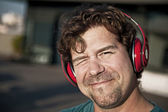 Portrait of a smiling man in red headphones — Stock Photo