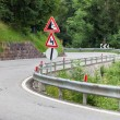 Stock Photo: Warning traffic sign on metal pole on winding road