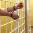 Постер, плакат: Prisoner in handcuffs locked in a cell