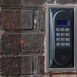 Old intercom on a red brick wall — Stockfoto
